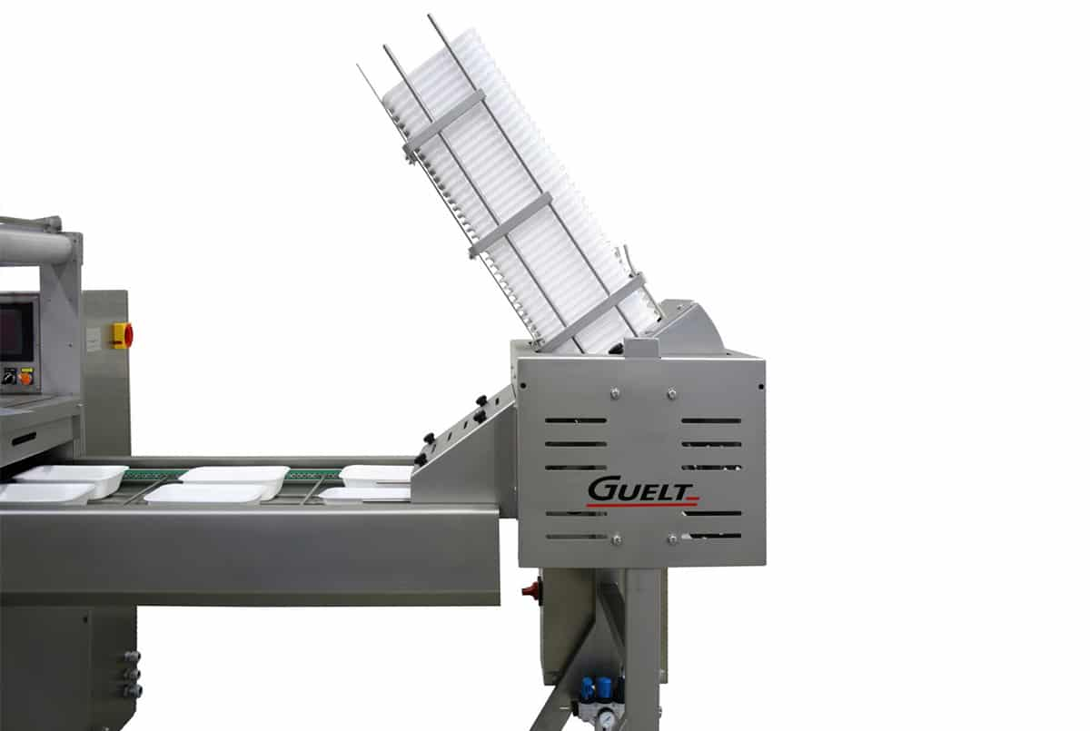 Tray unstacker fixed onto a tray sealing machine - Packaging solutions - Guelt